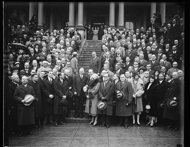 Educators meet Hoover. Members attending the 16th Annual meeting of the Association of American Colleges meet President Hoover and pose for this photograph on the steps of the temporary executive offices, the State, War and Navy building. In the center of the group, left to right: Robert L.Kelly, permanent executive officer of Alabama, President Hoover and Guy E. Snavely, President of the Association