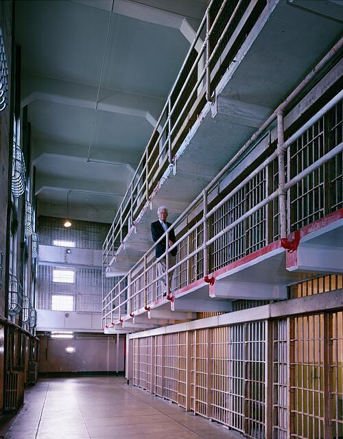 Former prison guard standing on balcony, inside Alcatraz Penitentiary, San Francisco, California
