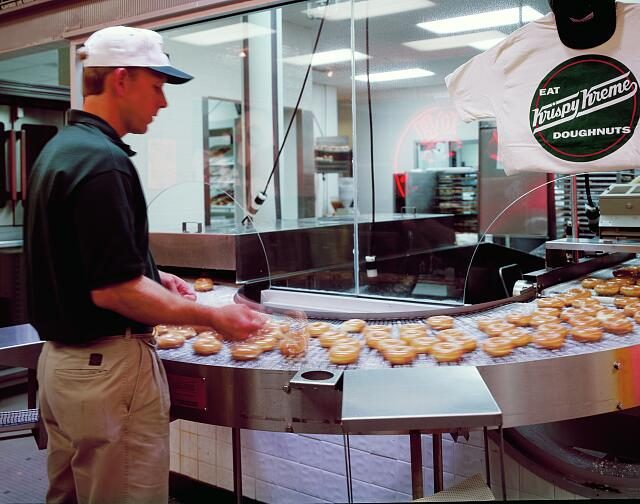 Employee watches the production line at the nation's first Krispy Kreme donut shop in Winston-Salem, North Carolina