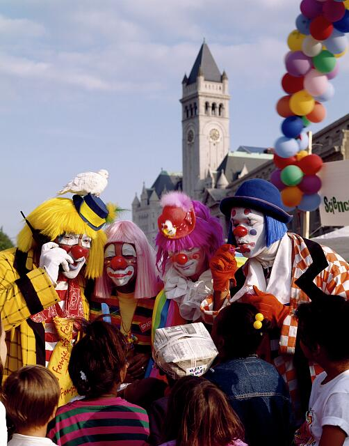 Clowns and kids on Pennsylvania Avenue during an event with the clock tower of the Old Post Office Building in the background. Washington, D.C.