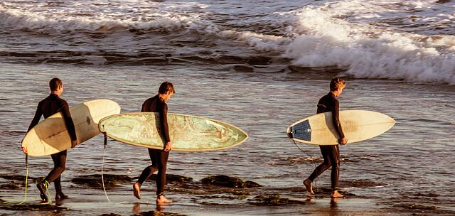 Three surfers take to the waves at Butterfly Beach in Montecito, a small city next to Santa Barbara, California