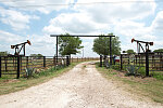 A ranch entrance, dramatically bracketed by oilfield pumpjacks, in Gonzales County, Texas