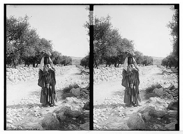 [Woman, possibly Bedouin, holding spindle, standing in road]