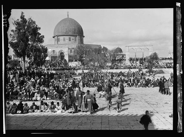 Moslems [i.e., Muslims] at prayer in mosque (Dome of the Rock) grounds at time of Mohammed Ali's funeral
