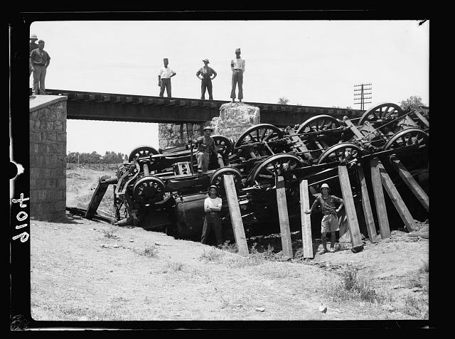 Palestine disturbances 1936. Locomotive turned turtle in a gully below a railroad bridge near Kefr-Jenuis