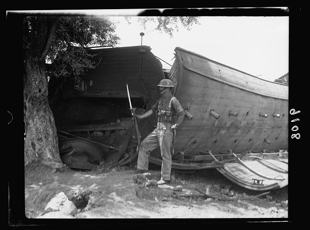 Palestine disturbances 1936. British soldier guarding the wreck [near Kefr-Jenuis]