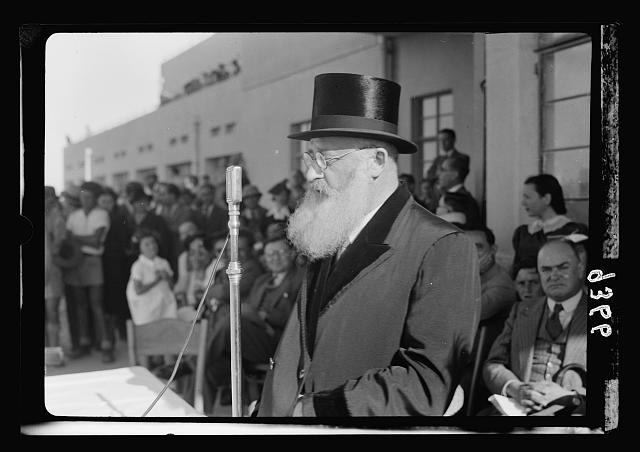 Wings over Palestine-Certificates of Flying School, April 21, 1939. Dr. Herzog, Chief Rabbi of Palestine (Askenazim) addressing gathering thro[ough] loudspeakers [Lydda Air Port]