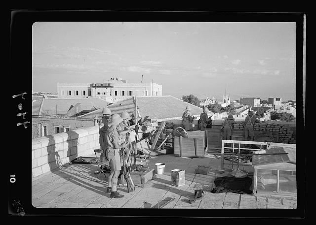 Troops operating from Nordia hotel bldg [i.e., building] overlooking Jaffa road and Barclays Bank, showing Tower of David in distance