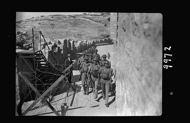 The raising of the siege of Jerusalem. Typical scene of troops in Old City before the lifting of curfew, squad of steel helmeted troops over top of south city wall