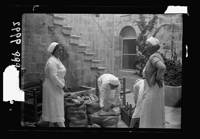 The raising of the siege of Jerusalem. Court-yard of the Anna Spafford Baby Home showing Mrs. Vester & nurses with baskets of bread for distribution among the poor of the quarter