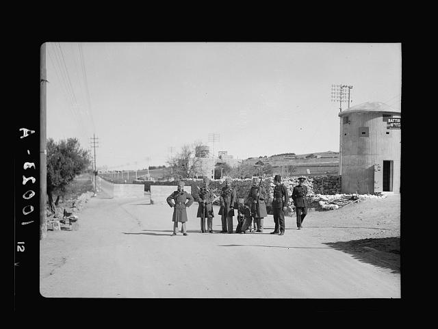 [Police and guards in road next to a concrete guard tower with sign pointing to Battir]