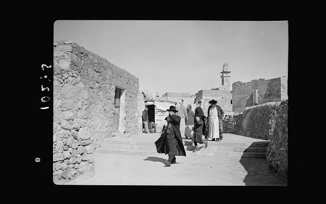 Orthodox Jews on their usual Sabbath walk to the Wailing Wall (showing Arabs in distance)