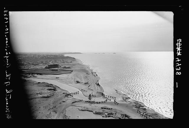Air views of Palestine. Jaffa, Auji River and Levant Fair. Mouth of the Auji River. Silhouette effect of camels fording. Jaffa promontory in distance