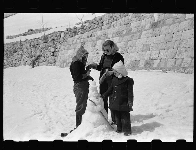 [Cedars. Photographic party stops for a cold snowy lunch. American youngsters build a snowman while waiting for lunch]