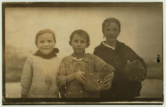 [3 of the many young oyster shuckers going home from the Pass Christian Cannery at 5 P.M. Lena Krueger, 7 years old (in the middle) had shucked 6 pots that day; Annie Kadeska, 9 years old on the right, has shucked 10 pots; and Rosie Zinsoska on the left (did not know her age) had shucked 6 pots.]  Location: [Pass Christian, Mississippi]