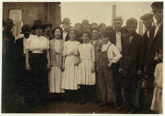[Group of workers, including boys and girls, standing outdoors]