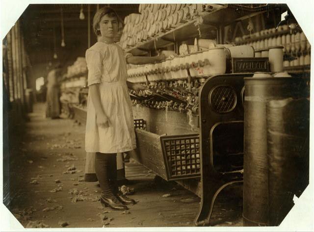 "Twelve year old Selina Wall working at spooling room in the Brazos Valley Cotton Mill, West, Tex. Their Family Record says she was born, March 23, 1901. Her mother said: ""She's just taking the place of her sister (fifteen years old). Selina could earn a dollar a day. She was raised up in a cotton mill over in Belton, but she has to stay home and do the cookin."" The mother and the fifteen year old girl work regularly in the mill. Several older boys work. Selina keeps house. Nine in the family.  Location: West, Texas."