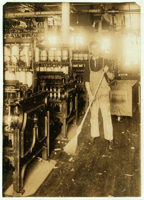 [Boy holding broom near textile machinery] Location: Fall River, Massachusetts.