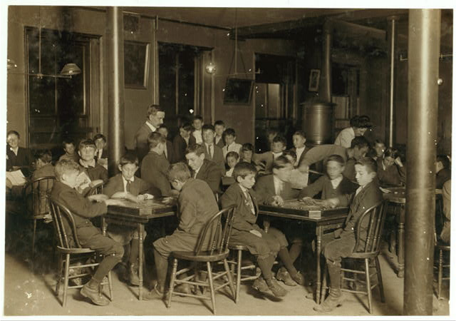 Name: In the Newsboys Reading Room. Boys seated at tables playing gamers. Boston 1915 Exhibit. Oct. 1909.  Location: Boston, Massachusetts.