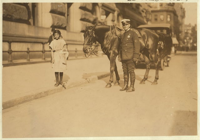 """Newsgirl, Park Row. Against the law, but """"who cares.""""  Location: New York, New York (State)"""