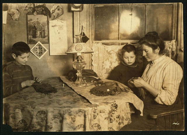 Late at night. Sewing tapes on gloves. The boy helps. Family of five sleep in room where the work is done. Location: New York, New York (State)