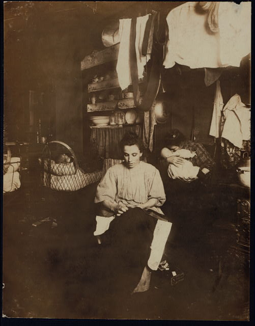 Mrs. Tony Racioppo, 260 Elizabeth St., N.Y. 1st floor rear, finishing pants in dirty tenement home. Althou[gh] it is a licensed house, the whole place is very much run down. The ahllway [i.e., hallway] is in the same condition as that one at 266 Elizabeth (see photo). Baby had bad cough. Mother said recovering from measles.  Location: New York, New York (State)
