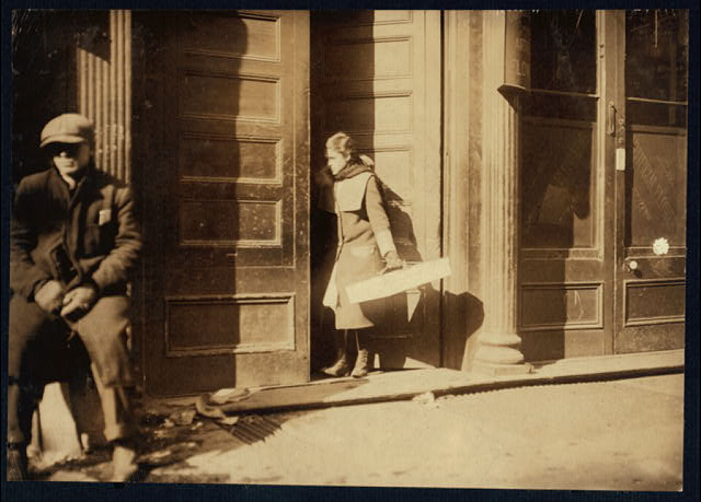 Noon. Girl entering the factory door, 526 W. Broadway, with artificial flowers made at home.  Location: New York, New York (State)