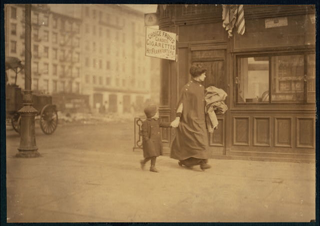 Mother and son carrying home-work. Near Astor Place, New York.  Location: New York, New York (State)