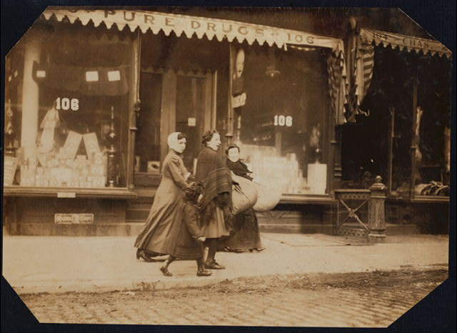 Woman and girl carrying finished couset covers made on Macdougal St.--to factory--171 Wooster Street, N.Y.  Location: New York, New York (State)