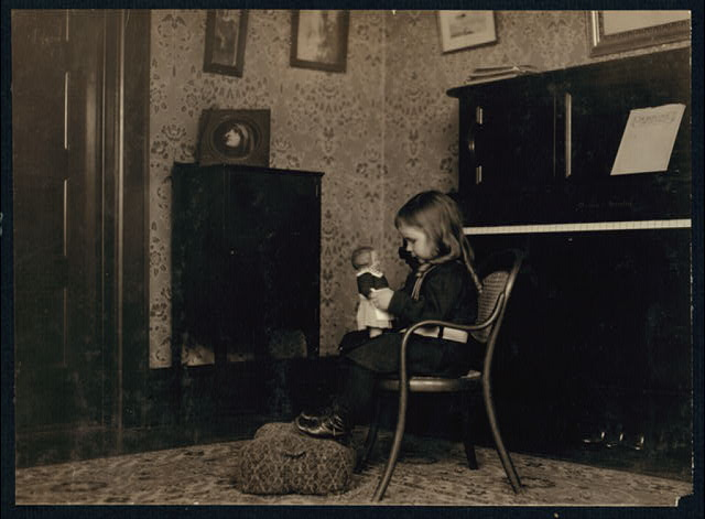 Little girl conversing with a Campbell Kid. See photos showing where they are made.  Location: New York, New York (State)