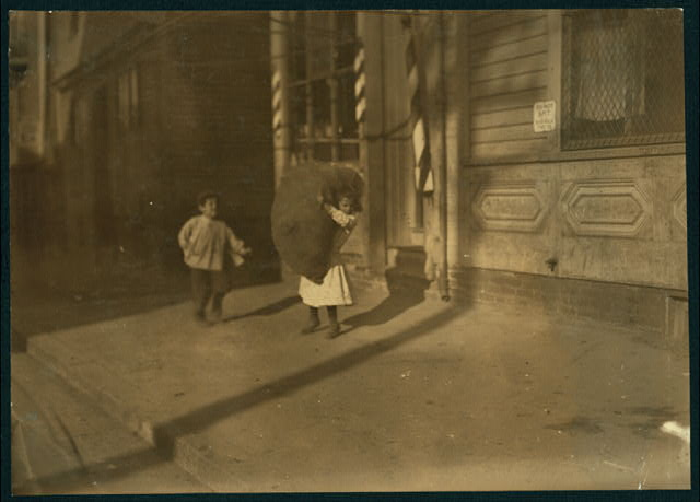 (For Child Welfare Exhibit 1912-13.) Tiny girl with big bag she is carrying home, Spruce St., Providence, R.I.  Location: Providence, Rhode Island.