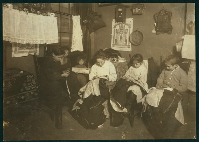 1 P.M. Family of Onofrio Cottone, 7 Extra Pl., N.Y., finishing garments in a terribly run down tenement. The father works on the street. The three oldest children help the mother on garments. Joseph, 14, Andrew, 10, Rosie, 7, and all together they make about $2 a week when work is plenty. There are two babies.  Location: [New York, New York (State)]