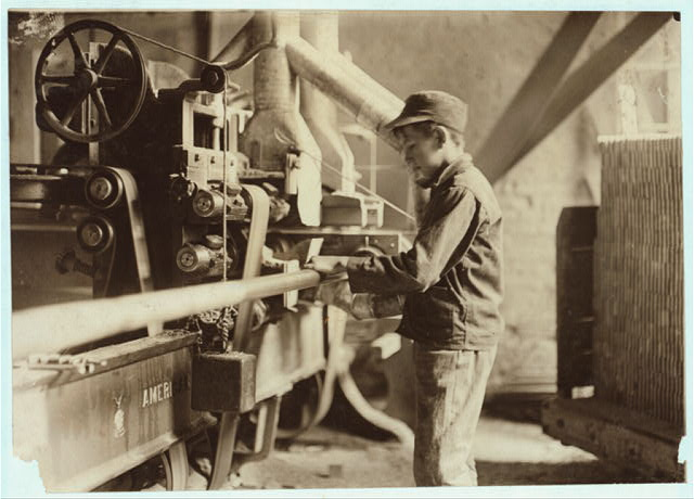 "Indiana Mfg. Co., Boy taking boards away from ""double cut-off"" machine. A Suggestive Name!.  Location: Peru, Indiana."