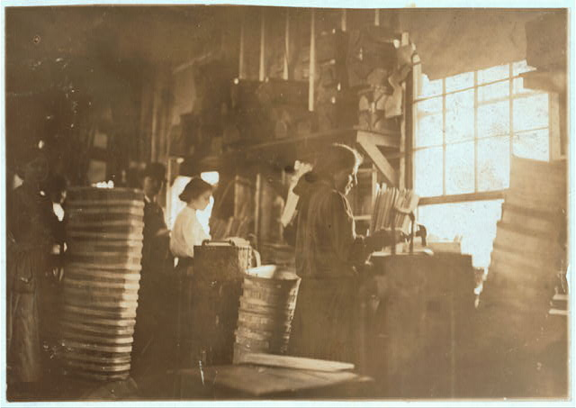 Girls making meat baskets. One probably under fourteen. A basket Factory.  Location: Evansville, Indiana.