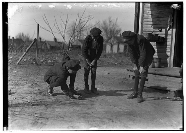 Brantley Henson (boy near porch). Been in mill 8 years. Jasper Henson, (in middle) Been in 3 years. Thedie Miller (Shooting). Been in 3 years. All doffers. Salisbury Cotton Mills, (N.C.)  Location: Salisbury, North Carolina.