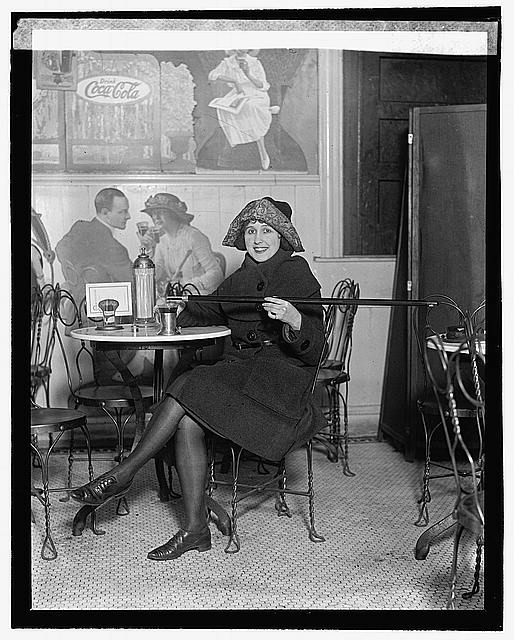 [Woman seated at a soda fountain table is pouring alcohol into a cup from a cane, during Prohibition; with a large Coca-Cola advertisement on the wall], 2/13/22