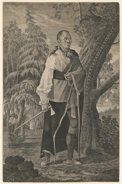 Portrait of Hendrick, Mohawk chief, full length standing holding tomahawk with camp scene in background