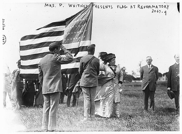 Mrs. P. Whitney presents flag at reformatory, [prison congress delegates in background]