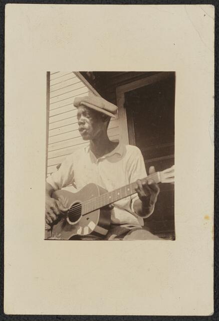 [Bill Tatnall, half-length portrait, seated, facing left, playing guitar, Frederica, Georgia]