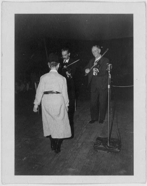 [Asa Helton and Fiddling Bill Hensley playing fiddle, unidentified woman in foreground, at the Mountain Music Festival, Asheville, North Carolina]