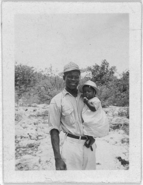 [Man holding child, standing, facing front, possibly from the visit by Alan Lomax and Mary Elizabeth Barnicle to Andros Island in the Bahamas]