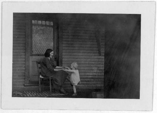 [Woman sitting on front porch with child]