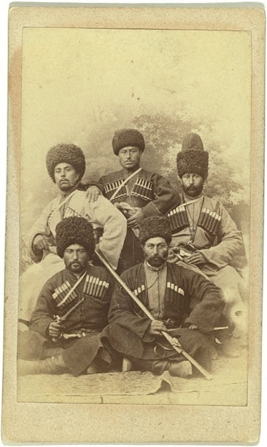 [Group portrait of five men, seated, facing front]
