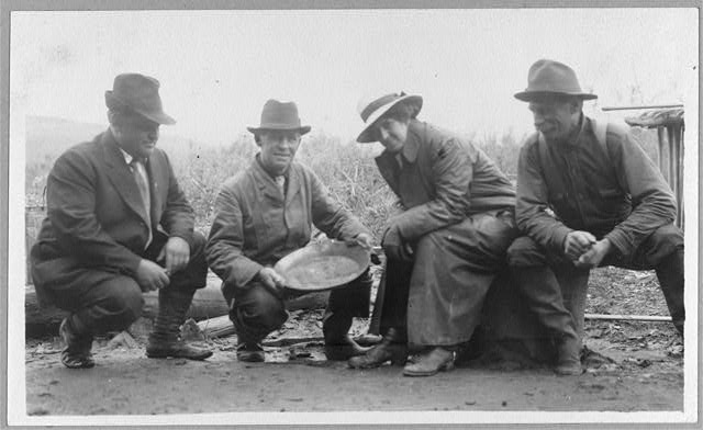 [Group portrait of a woman and three men, crouched outside, smiling; one of the men is displaying a dish of panned gold]