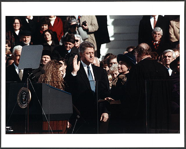 [Bill Clinton, standing between Hillary Rodham Clinton and Chelsea Clinton, taking the oath of office of president of the United States]