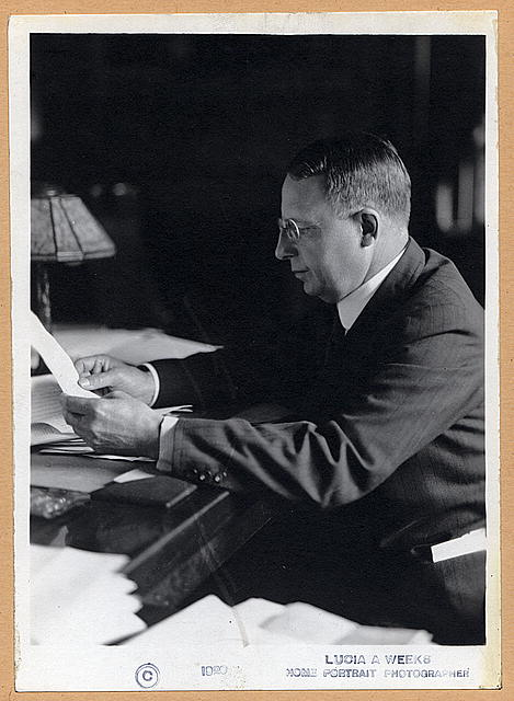 [James M. Cox, Governor of Ohio, half-length portrait, facing left, seated at desk, reading]