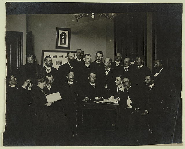 [Frances Benjamin Johnston, seated in profile at left, group portrait with 18 unidentified men]