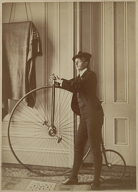 [Frances Benjamin Johnston, full-length self-portrait dressed as a man with false moustache, posed with bicycle, facing left]