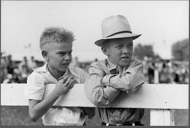 Two boys leaning on fence watching parade, state fair, Donaldsonville, Louisiana
