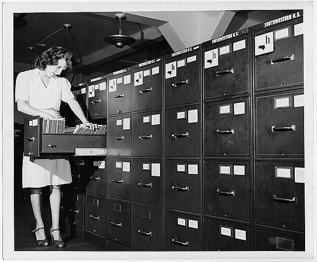 Jeannette Poirier looking at photographs in file cabinet drawer at the Washington office of the Overseas Branch of the U.S. Office of War information